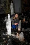 Mann mit einer brennenden Kerze sitzt in einer Höhle mit Eisblöcken Lizenzfreie Stockbilder