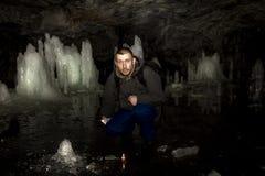 Mann mit einer brennenden Kerze sitzt in einer Höhle mit Eisblöcken Lizenzfreies Stockbild