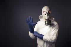 Mann mit einer Gasmaske, die auf seine Handschuhe sich setzt Stockbild