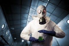 Mann mit einer Gasmaske, die radioaktive Flüssigkeit anhält Stockbilder