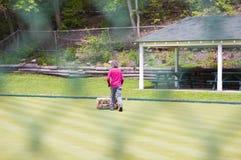 Mann mit einer Rasenmähmaschine hinter einem Zaun Stockfoto