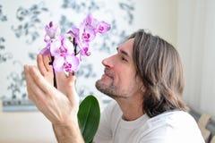 Mann mit einer rosa Orchidee im Raum Stockbild