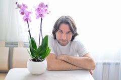 Mann mit einer rosa Orchidee im Raum Lizenzfreies Stockbild
