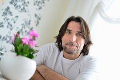 Mann mit einer rosa Orchidee im Raum Lizenzfreies Stockfoto