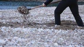 Mann mit einer Schaufelgrabung ein Graben auf dem Strand stock footage
