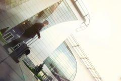 Mann mit einer Tasche auf Rädern am Flughafen Stockbild