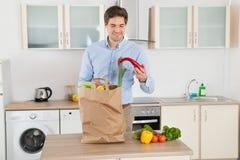 Mann mit Einkaufstüte im Küchen-Raum Stockbilder