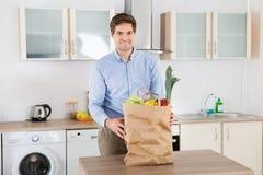 Mann mit Einkaufstüte im Küchen-Raum Stockfoto