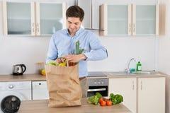 Mann mit Einkaufstüte im Küchen-Raum Stockbild