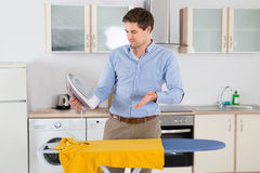 Mann mit elektrischem Eisen und T-Shirt im Küchen-Raum Stockfoto