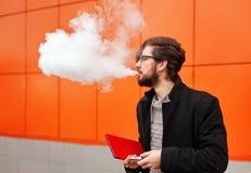 Mann mit elektronischer Zigarette und Tablet-PC Lizenzfreie Stockfotos