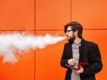 Mann mit elektronischer Zigarette und Tablet-PC Stockbilder
