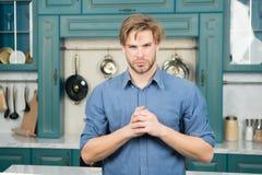 Mann mit ernstem Gesichtsstand mit den gefalteten Fingern in der Küche Stockbilder