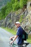 Mann mit Fahrrad auf Gebirgsreise Stockbild