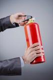 Mann mit Feuerlöscher - feuerbekämpfendes Konzept Stockbild