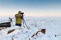 Mann mit Fotokamera auf dem Stativ, der timelapse Fotos in der arktischen Tundra macht Lizenzfreie Stockbilder