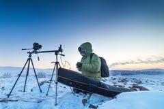 Mann mit Fotokamera auf dem Stativ, der timelapse Fotos in der arktischen Tundra macht Lizenzfreies Stockbild