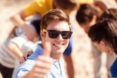 Mann mit Freunden auf dem Strand, der sich Daumen zeigt Stockfotos