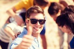 Mann mit Freunden auf dem Strand, der sich Daumen zeigt Lizenzfreie Stockbilder