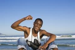 Mann mit Fußball-Stiefeln um Hals zujubelnd auf Strand Stockfotos