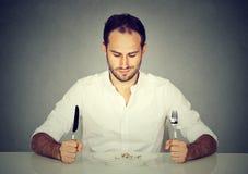 Mann mit Gabel und Messer, das bei Tisch sitzt, leere Platte betrachtend Lizenzfreies Stockfoto