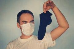 Mann mit Gasmaske hält stinky Socke - unangenehmes Geruchkonzept lizenzfreie stockfotos