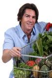 Mann mit Gemüselaufkatze Stockfotos