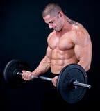 Mann mit Gewichten eines Stabes in den Händen Lizenzfreie Stockfotos