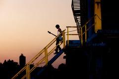 Mann mit Gitarre an der Dämmerung Stockbilder