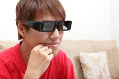 Mann mit Gläsern 3D auf dem Überwachen des Films 3D Stockfotos