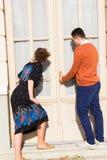 Mann mit Gläsern in der orange Strickjacke mit der Frau, die zum ope versucht Stockbild