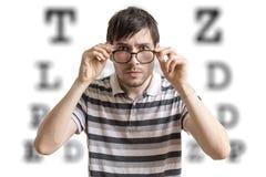 Mann mit Gläsern prüft seinen Anblick Diagramm für Augenanblickprüfung im Hintergrund lizenzfreies stockfoto