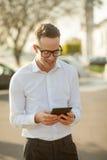 Mann mit Gläsern sprechen am Handy in den Händen Lizenzfreies Stockfoto