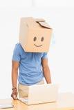 Mann mit glücklichem smileykasten über Gesicht vor Laptop Stockfoto