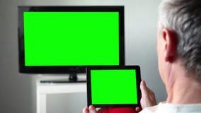 Mann mit grünem Schirm Ipad sieht fern stock footage