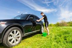 Mann mit grüner Eimer-waschendem Auto auf dem grünen Gebiet Stockfotos