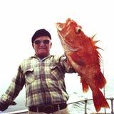 Mann mit großem orange Yelloweye-Klippenbarsch lizenzfreie stockbilder