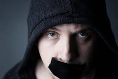 Mann mit Haube und bedeckter Mund durch schwarzes Band Stockfotografie