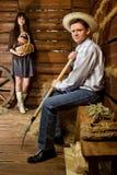 Mann mit Heugabel in der Strohhutfrau mit Korb Lizenzfreie Stockfotos