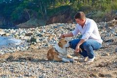 Mann mit Hund im weißen Hemd, das am Strand sitzt Stockfoto