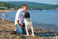 Mann mit Hund im weißen Hemd, das am Strand sitzt Lizenzfreie Stockbilder