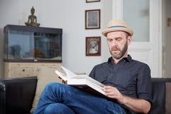 Mann mit Hut ein Buch in seinem verlassenden Raum lesend Lizenzfreie Stockbilder