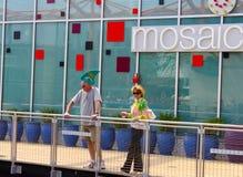 Mann mit Hut und Frau Landshark mit Getränk auf dem Balkon, der unten mit Reflexion von den Leuten partying sind P betrachtet stockfotos