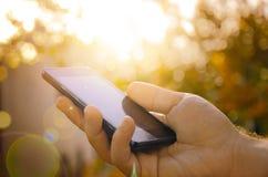 Mann mit intelligentem Telefon an Hand, unscharfer Hintergrund Stockfotos