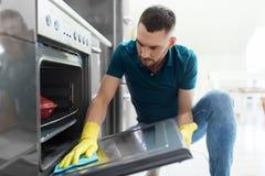 Mann mit Küche der Lappenreinigungsofen-Tür zu Hause Stockfoto