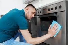 Mann mit Küche der Lappenreinigungsofen-Tür zu Hause Stockfotografie