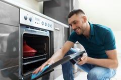 Mann mit Küche der Lappenreinigungsofen-Tür zu Hause Lizenzfreies Stockbild