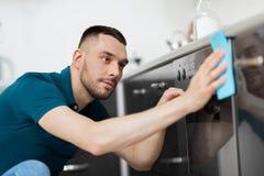 Mann mit Küche der Lappenreinigungsofen-Tür zu Hause Stockbild