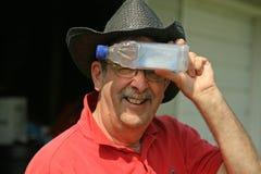 Mann mit kalter Flasche auf seiner Stirn Lizenzfreie Stockfotos