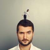 Mann mit kleinem Mann auf dem Kopf Stockfotografie
